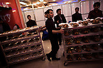 Hundreds of family members and friends - carefully divided between side's for men and women - attend a wedding at the lavish Mumtaz Majal wedding hall in Kabul. Glistening wedding halls dot the Kabul city scape and their attendance - which always includes large dinners and energetic dancing - is a mainstay of Kabuli social life. Here waiters wait to assemble their various carts of food bearing hundreds of fried chickens and plates of rice, fruit, kebab, and other Afghan dishes entering the main hall. Summer 2010.