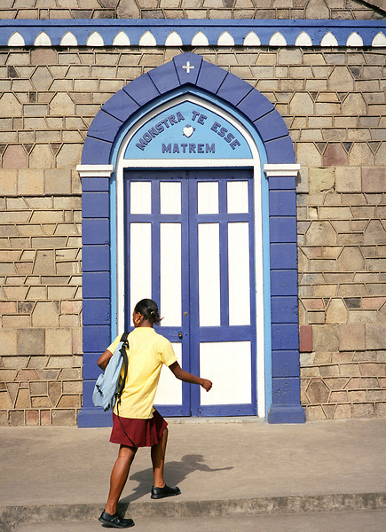 A teenage schoolgirl walks by the Church of the Assumption of the Blessed Virgin Mary on the town square in Soufriere. St. Lucia.