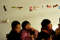 CHINA. Beijing. Young orphans in an orphanage outside of Beijing. 2007. The orphanage is a mix of orphans and children left for long periods of time by migrant workers who cannot take their children with them. There are currently millions of orphans in China living in orphanages spread throughout the country. As a result of China's one-child policy, many children are abandoned or given up if they suffer from any physical or mental handicap as the parents strive to have a child born 'normal' and well. This has led to may children being abandoned to live in state and privately-owned orphanages.