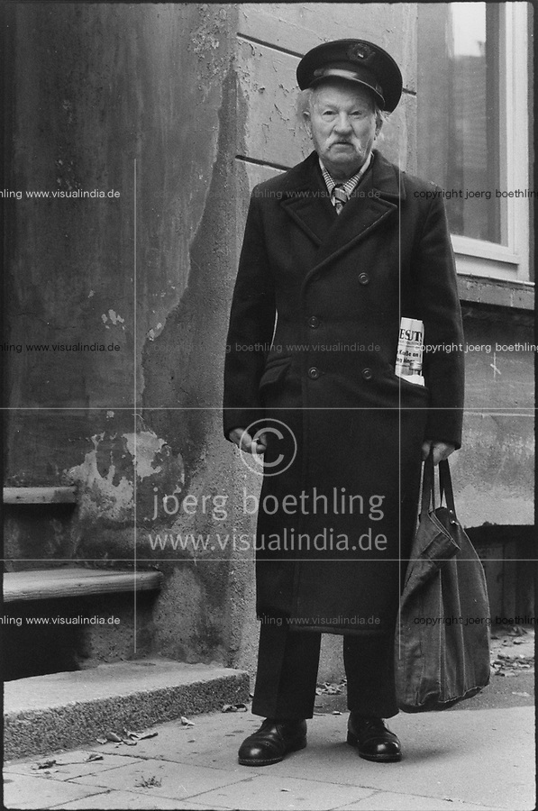 EAST GERMANY, GDR German Democratic Republic 1987, Wismar, old man with newspaper of communist party SED, liquor bottle and shopping bag / DDR Deutsche Demokratische Republik 1987, Wismar, alter Mann mit Schiffermütze, in der Hand Einkaufsbeutel, in der Mantel Tasche die SED Zeitung Neues Deutschland und Schnapsflasche- copyright Joerg Boethling, also as signed black white Baryt fine print available!