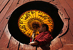 Novice Buddhist monks framed by oval windows by Sabina Atker