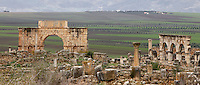 Triumphal Arch and ruins of Forum, Volubilis, Morocco, pictured on December 25, 2009. The massive arch, 217 AD, was built in honour of Caracalla, Roman Emperor 211-217. Ruined Ionic columns of the Forum lining the Decumanus Maximus, Volubilis, Morocco, pictured on December 25, 2009. The huge stone blocks may have been pedestals for statues. Around the city fertile plains providing agriculural produce stretch towards the mountains. Volubilis, founded in the 3rd century BC was an important city in the Western part of Roman North Africa. The Romans abandoned it in the 3rd century AD. Excavations were started by the French in 1915, and it became a UNESCO World Heritage site in 1997. Picture by Manuel Cohen