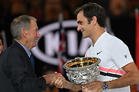 January 28, 2018: Number two seed Roger Federer of Switzerland accepts the winner's trophy from Ashley Cooper (who won the tournament 60 years ago) after winning the Men's Final against number six seed Marin Cilic of Croatia on day fourteen of the 2018 Australian Open Grand Slam tennis tournament in Melbourne, Australia. Federer won 3 sets to 2. Photo Sydney Low