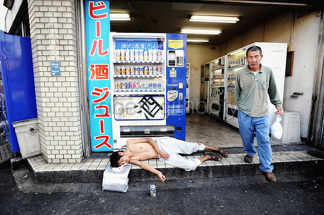 """A homeless man lies outside a booth containing several  automatic vending machines selling alcoholic  drinks the Kamagasaki district of Osaka, Japan. Alcoholism afflicts a sizable portion of the city's homeless, with drinks machines such as those shown in this picture selling almost entirely low-priced beers and """"sake"""", a wine-like beverage fermented from rice.."""