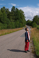 Country road. A person walking on the road. Warming in the sunshine. Smaland region. Sweden, Europe.