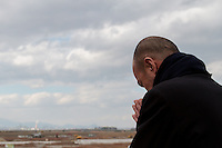A man parys as he looks out over the tsunami devastated landscape from a  shrine on top of Hiyori yama  or Weather Hill to remember victims of the tsunami at  Miyagi, Japan. Friday March 11th 2016. 2016 marks the fifth anniversary of the Great East Japan earthquake. This magnitude 9 quake caused a tsunami that flattened large parts of the Tohoku coast killing around 18,000 people and triggering a nuclear disaster at Fukushima Daichi Power Station.
