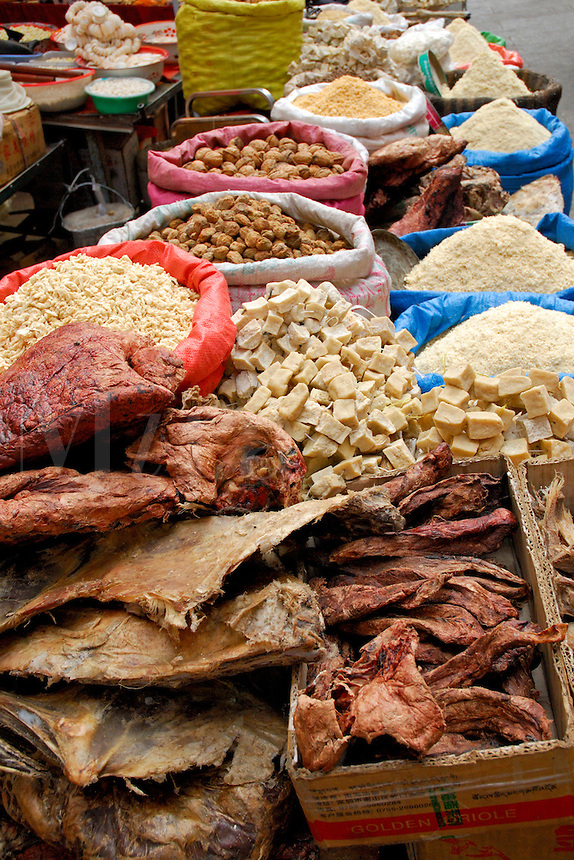 Dried yak meat, cubes of yak cheese, or chura, and roasted barley flour, or tsampa.  Typical Tibetan staples at a Tromsikhang market stall in the Barkhor area of the Tibetan quarter, Lhasa, Tibet.