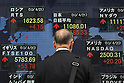 Apr 21, 2010 - Tokyo, Japan - A pedestrian looks at an electronic stock board outside a securities firm in Tokyo, Japan, on April 21, 2010. The 225-issue Nikkei Stock Average gained 168.09 points, or 1.54 percent, from Tuesday at 11,068.77.