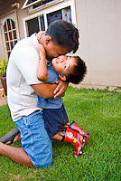 Local dad hugging 3 year old son in front yard of their home, Makakilo, Oahu