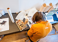 A final-year furniture design student working and sketching out pieces as well as using wood blocks to build models.