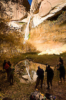 A group of photography students photograph early light on Calf Creek Falls, and its reflection in a nearby pond. The falls are a three-mile trail in the Calf Creek Recreation Area near Grand Staircase-Escalante National Monument in southern Utah.