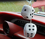 A bit of nostalgia! Whtie fluffly dice hand off the rearview mirror standing out against the red dash of a 1964 Chevrolet Impala at the 2010 Wings 'n' Wheels Showcase, Galway, New York.