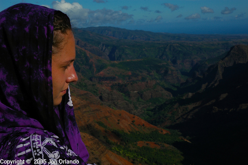 A woman overlooks a canyon on the island of Kauai, Hawaii.  Shot on location for Idanha Films