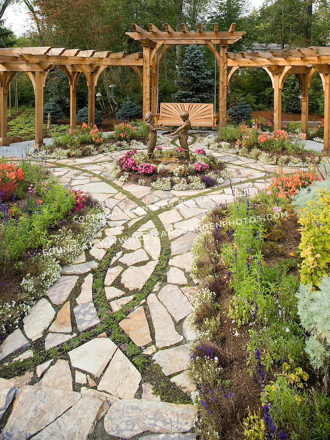 An intricate stone pathway inlaid with curving bands of stepable, perennial groundcovers leads to a wooden garden swing.  This image is available through an alternate architectural stock image agency, Collinstock located here: http://www.collinstock.com