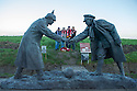 "25/12/14<br /> <br /> Football fans from around the world pay their respects by a sculpture depicting two WW1 soldiers playing football during the famous Christmas Day truce in the field near Messine, Belgium, close to where the match was played in Flanders, Belgium.<br /> <br /> The sculpture, made in England, arrived in Flanders on Christmas Eve, and was first displayed in the town centre before being taken to the spot where the match was played. <br /> <br /> Sculpted by Andy Edwards the work is entitled 'All Together Now', recalling the song by the band The Farm - which was inspired by the truce. <br /> <br /> Chris Butler said: ""Castle Fine Arts are proud to have cast a number of war memorials over the years. We are honoured to support this sculpture for peace. I believe it will touch the hearts of millions.""<br /> <br /> <br /> ""It will be a symbol of peace and hope and a call for a renewed worldwide cessation of violence in honour of those brave boys who 'joined together and decided not to fight'"".<br /> <br /> <br /> The statue depicts the meeting of a British and a German soldier over a football, deep in the mud between the lines on that first Christmas of the war. The soldiers appear to be shaking hands but  are not not quite touching, forming a space in which a visitor can insert their own hand to complete the union.  A chance for a moments reflection on how far we are from true peace and brotherhood and the part each of us has to play in that dream. We want the work to stand as both a celebration of this inspirational and heroic event and as symbol of hope and peace. <br /> <br /> The project was instigated some years ago, with the support of the Football Asscociation (FA), as football's contribution to the First World War commemorations. <br /> <br /> All Rights Reserved - F Stop Press. www.fstoppress.com. Tel: +44 (0)1335 300098"