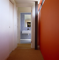 One wall of this corridor leading to a tiled bathroom has been painted a dark orange