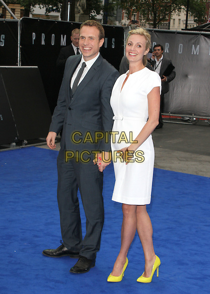 Rafe Spall and Elize du Toit.World Premiere of 'Prometheus' at the Empire, Leicester Square, London, England..May 31st, 2012 .full length dress grey gray suit holding hands white married husband wife yellow shoes .CAP/ROS.©Steve Ross/Capital Pictures.
