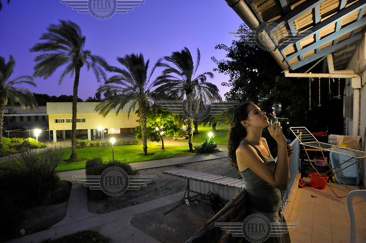 A young woman blows soap bubbles on her balcony in the Degania Kibbutz, the first Israeli kibbutz, founded in 1910 by Russian immigrants.