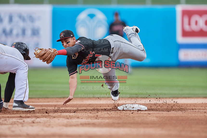 Daniel Castro (1) of the  Albuquerque Isotopes stretches for the ball as Jabari Blash (36) dives for the bag at Smith's Ballpark on April 8, 2018 in Salt Lake City, Utah. Blash was caught in the rundown for the out. Albuquerque defeated Salt Lake 11-4. (Stephen Smith/Four Seam Images)