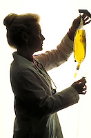 Silhouette of nurse adjusting an IV bag.