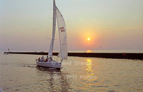A sailboat gliding into harbor as the sun sets.