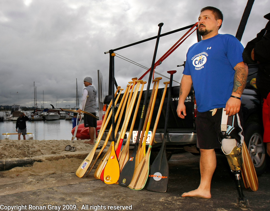 Saturday, 01/24/09.  Campland on the Bay, Mission Bay, San Diego, CA, USA.  Greg Crouse (r) stands by a row of outrigger canoe paddles as he and Carlito Butlid (c) prepare for a paddle on Mission Bay during an event sponsorded by the Challenged Athletes Foundation.  Both men are missing all or part of one leg but regularly participate in outrigger canoeing.  The pari drove from Newport Beach to assist with the event where  participants had the opportunity to try several different paddle sports.   The Challenged Athletes Foundation established the Operation Rebound fund to provide sports opportunities and support for troops, veterans and first responders who have suffered permanent physical injuries in the line of duty.