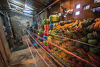 Myanmar, Burma, Bago District, Taungoo. Daw Khin Nilar Htun makes plastic rope. She used to work in a factory that made this rope, and they remodeled this machine after that one. In the factory they made only two strings of ropes but this machine that she created herself makes four strings of rope at a time. She made the design, her husband and cousin welded it together. She makes about 70 bunches a day, each bunch has ten ropes, her husband helps by selling the rope in the market and they make $2-5 a day. He also sells clay pots that he gets from others.  She work about 7.5 hours a day but has to hire some help as she also cooks, cleans and takes care of the children. They have five children ages 4-24. She received a BRAC loan of $500 and was able to open a small restaurant as well and now together with the restaurant, selling the rope and pots they make about $55 a day. They had a storage place but they lost everything in a fire, had no insurance.  She bought materials for the rope with the initial BRAC loan but wants to get another loan to get a new machine and try and replace the stock that was lost. The father would like to bring up the standard of the family. One daughter is an engineer and another is a nurse. Model released, MR-Myanmar-138, 137.