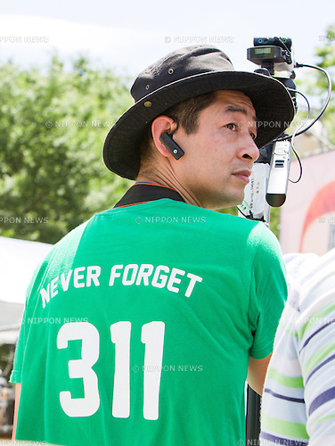 "July 16, 2012 - Tokyo, Japan - A journalist wearing a ""never forget 311"" t-shirt looks about during the massive 100,000 people's call demanding the abolishment of all nuclear power plants. Since the recently resumed operations of the Oi Nuclear Power Plant in Fukui Prefecture, has attracted an ever growing number of anti-nuclear demonstrators in a call to stop all forms of nuclear energy. (Photo by Christopher Jue/AFLO)"