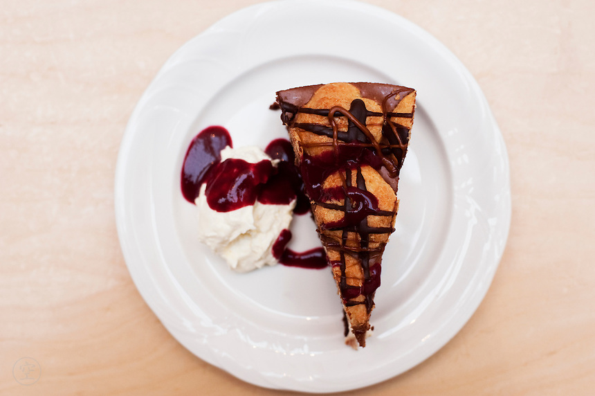 Chocolate and raspberry cheesecake served with sauce and whipped cream.