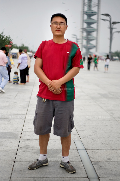 Zhangnanwei, a petroleum worker, age 29, poses for a portrait in Beijing. Response to 'What does China mean to you?': 'Home, mother.'  Response to 'What is your role in China's future?': 'To protect the environment and estuaries.'