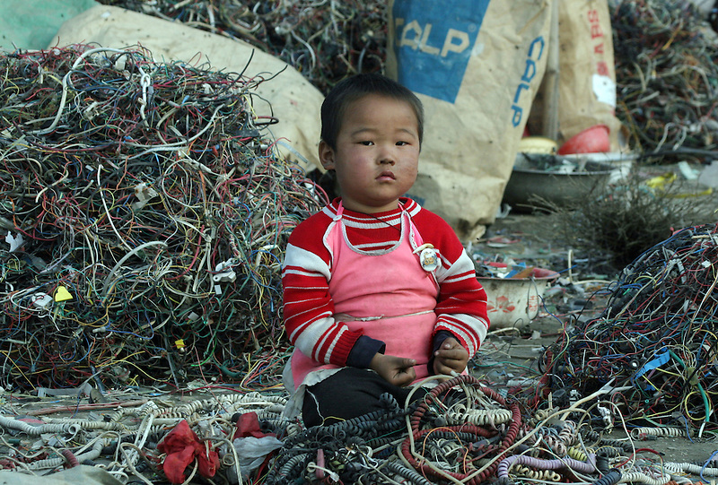 A child plays in a junkyard where wires of electronic trash are stripped in Guiyu, China March 8, 2005. For years, developed countries have been exporting tons of electronic waste to China for inexpensive, labor-intensive recycling and disposal. Since 2000, it's been illegal to import electronic waste into China for this kind of environmentally unsound recycling.