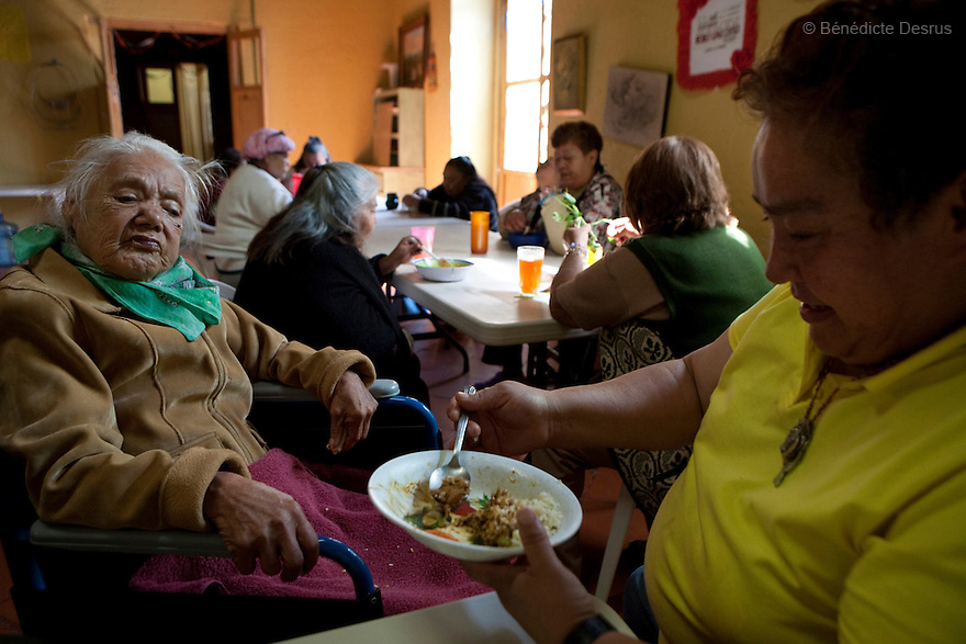 Patricia, a resident of Casa Xochiquetzal, helps Consuelo eat her meal at the shelter in Mexico City, Mexico on November 17, 2008. Casa Xochiquetzal is a shelter for elderly sex workers in Mexico City. It gives the women refuge, food, health services, a space to learn about their human rights and courses to help them rediscover their self-confidence and deal with traumatic aspects of their lives. Casa Xochiquetzal provides a space to age with dignity for a group of vulnerable women who are often invisible to society at large. It is the only such shelter existing in Latin America. Photo by Bénédicte Desrus