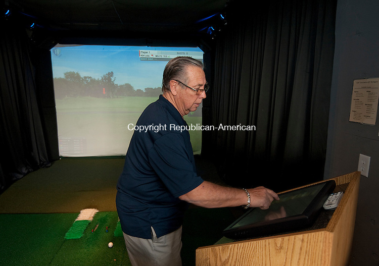 TORRINGTON,  CT-111716JS02- Buzz Ebner, co-owner of Mulligans, a sports bar and indoor driving range at Eastwoods Country Club in Torrington, demonstrates one of the games  on Thursday. Jim Shannon Republican American