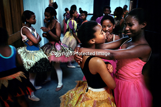 'Dance for All' students chat backstage as they prepare for an annual recital in Guguletu, South Africa. Cape Town City Ballet began the programme in the poor squatter camps outside the city. Some 200 children aged 6 to 18 now dance three times a week. (Photo by: Per-Anders Pettersson)