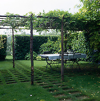 A wisteria covered pergola provides shade for a table and chairs in this formal garden