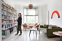 Jimi Lee in her modernised Victorian sitting room with a bay window and painted floorboards. The room is furnished in a retro style with a green sofa, coffee table and two armchairs. One wall houses floor to ceiling book shelves.