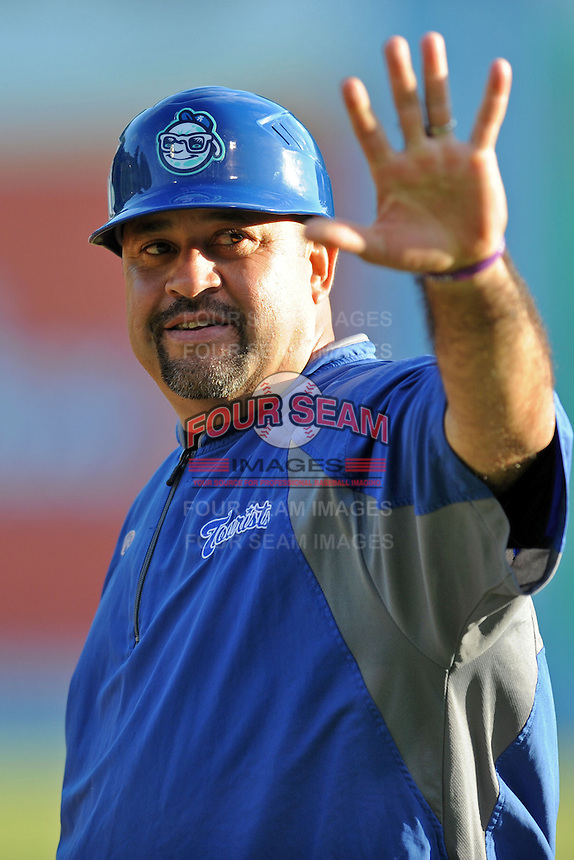Asheville Tourists  manager Fred Ocasio #28 waves to fans during a game against the Hagerstown Suns at McCormick Field on May 28, 2013 in Asheville, North Carolina. The Tourists won the game 9-4. (Tony Farlow/Four Seam Images)