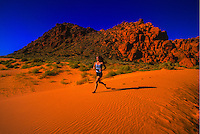 Woman running in the sand dunes, Snow Canyon State Park, near Ivins (near St. George), Utah