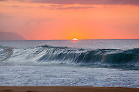 A wave breaks before an orange sunset at Ke Iki Beach, North Shore, O'ahu.