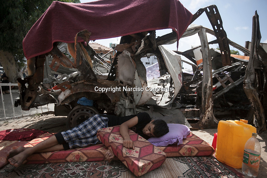 "In this Saturday, Aug. 16, 2014 photo, a Palestinian child sleeps beside the wreckage of an ambulance at the entrance gate of Al-Shifa Hospital in Gaza City during the five days truce of the ongoing ""Protective Edge"" Israeli military operation in Gaza Strip. (Photo/Narciso Contreras)"