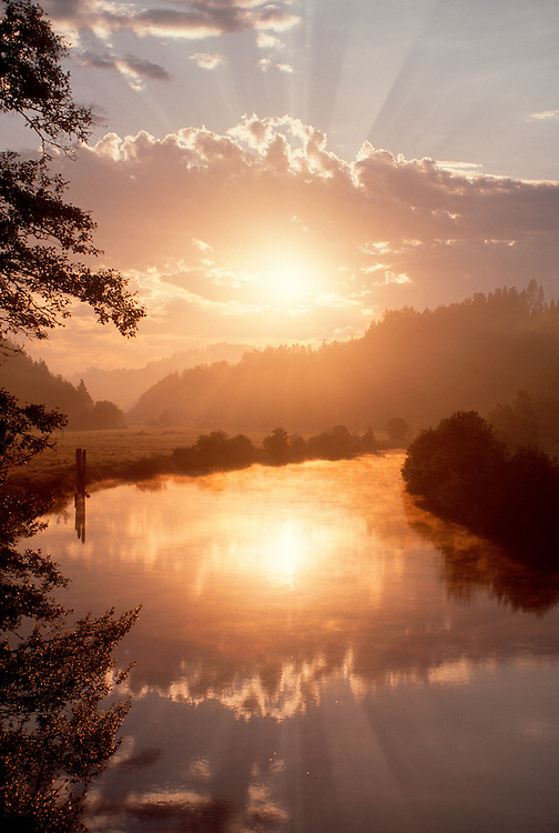 Coos River, Oregon, Inspirational image of rays of sun over pastoral river and hills.
