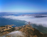 aerial photograph of fog moving across the Golden Gate bridge with the Marin headlands in the foreground and San Francisco in the background