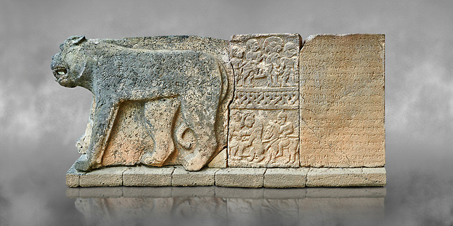Pictures & images of the North Gate Hittite sculpture stele depicting Hittite Gods. 8th century BC. Karatepe Aslantas Open-Air Museum (Karatepe-Aslantaş Açık Hava Müzesi), Osmaniye Province, Turkey. Against grey art background