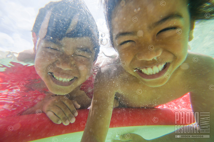 Young kids smiling underwater during surf session