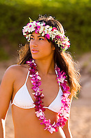 A half length view of a pretty local girl wearing a haku orchid lei and a standard orchid lei at Wailea, Maui.