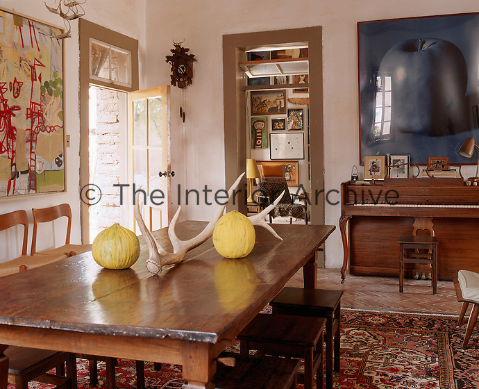 The dining room features a painting by Matt Cotten and an apple photograph by Adam Light and the table is made from Indonesian teak floorboards