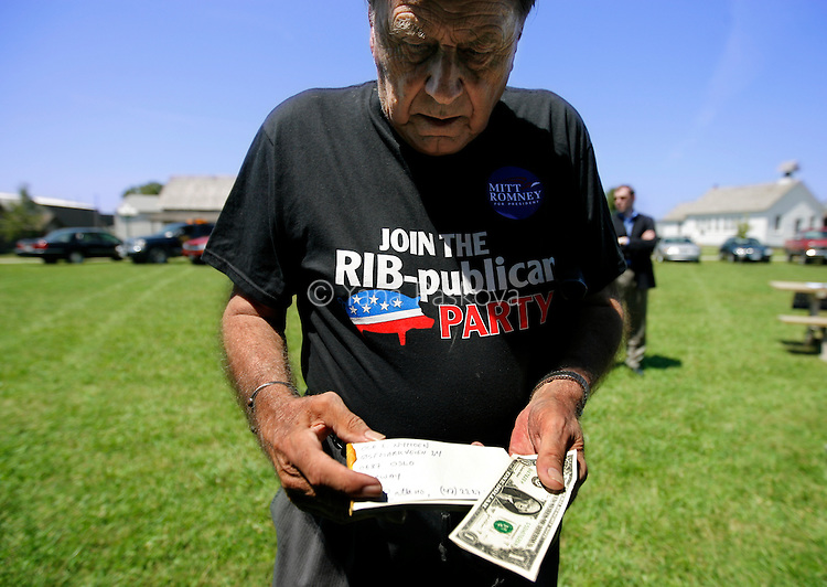 A potential supporter of U.S. Presidential candidate Mitt Romney (R-MA) goes through his belongings as the politician campaigns with his family in Forest City, IA, on July 21, 2007.