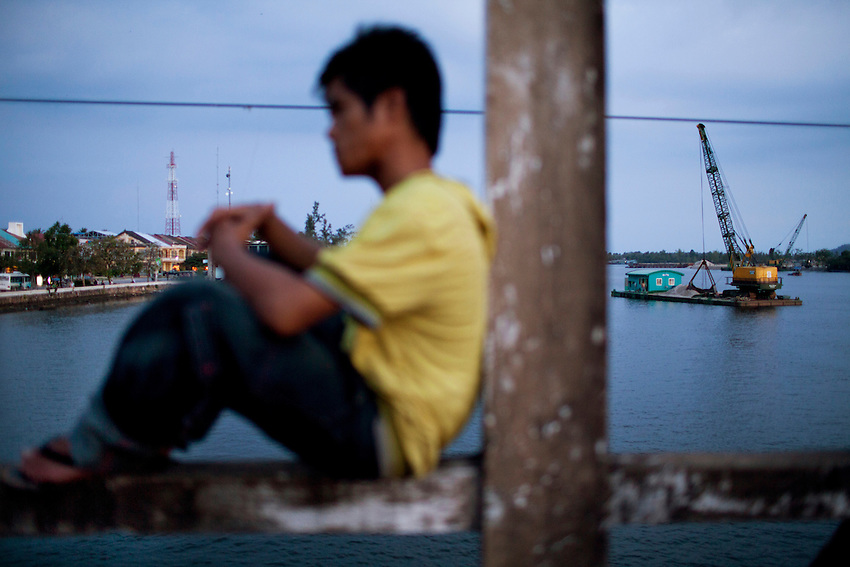 A man sits on a bridge over the Kampong Bay estuary in Kampot town, Cambodia, March 9, 2012. In the background, a sand dredging crane is moored.