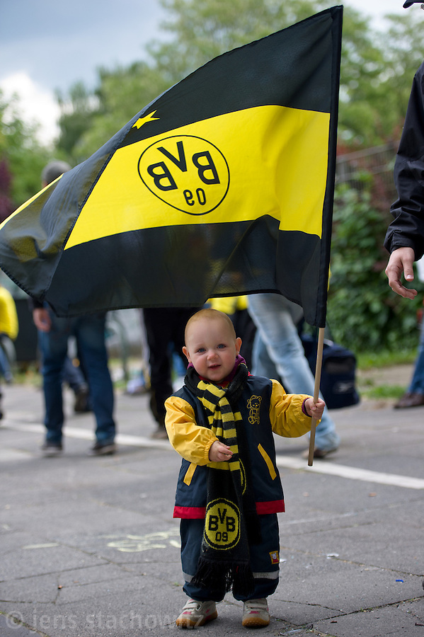 A very young child is waving a flag. - In Dortmund fans celebrated a gigantic party because of the title win of their favorite soccer club BVB 09 in the German Premium League.