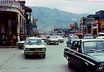 Cars and trucks against the background of stores and hills of the capital. Images of the capital,Port au Prince, Haiti 1975